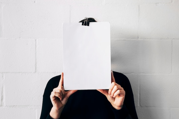 A female holding white paper in front of her face against white wall Free Photo