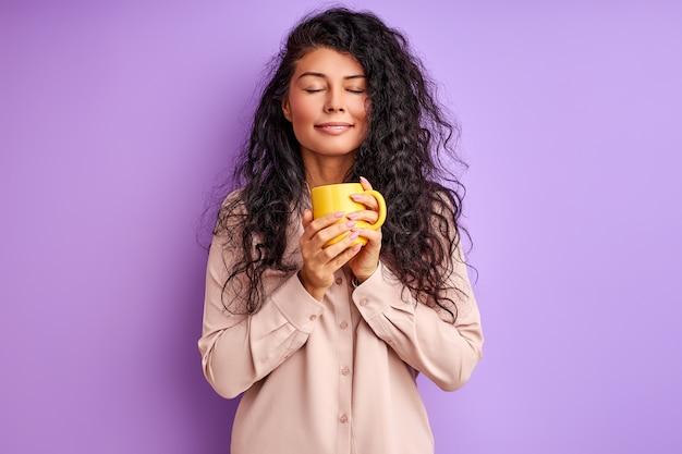 Женщина держит желтую кружку в руках, расслабляясь, пьет кофе или чай по утрам, наслаждаясь закрытыми глазами Premium Фотографии