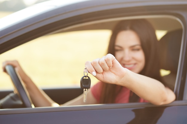 Female holds key while sits in luxury automobile, glad to recieve expensive present from relatives, focus on keys Free Photo
