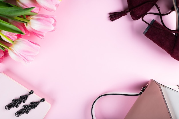 Female home office desk. workspace with notebook, pink tulip flowers and accessories. flat lay, top view. fashion blog background. fashion concept. Premium Photo