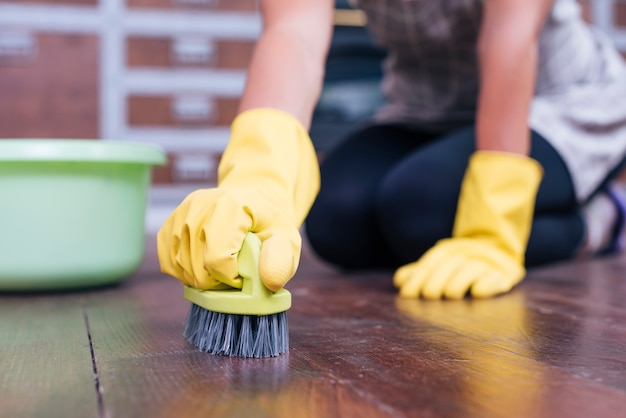 Female housekeeper cleaning hardwood floor with brush wearing yellow gloves Free Photo