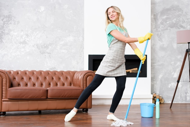 Female housekeeper wearing apron dancing with mop while doing housework Free Photo