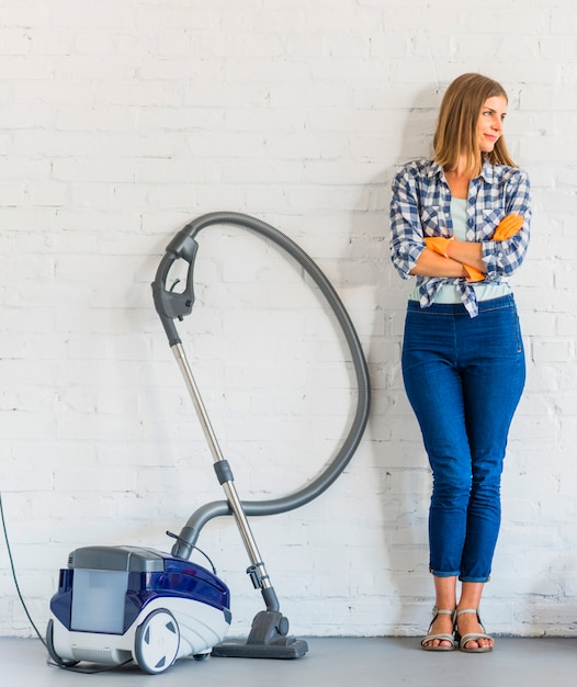 Female housemaid standing near vacuum cleaner in front of brick wall Free Photo