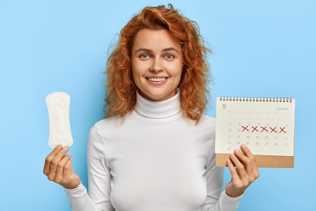 Female hygiene concept. redhead smiling woman holds clean period sanitary napkin pad and menstruation calendar Free Photo