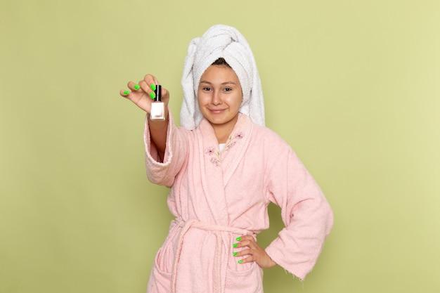 マニキュアを保持しているピンクのバスローブの女性 無料写真