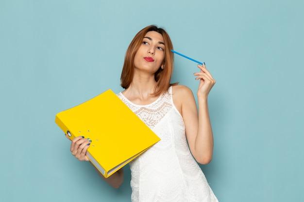 Женщина в белой блузке и синих джинсах держит желтые файлы Бесплатные Фотографии