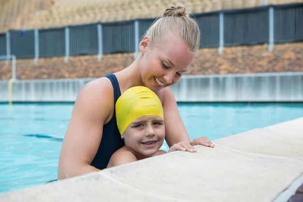 Женский инструктор и молодой мальчик отдыхают у бассейна Premium Фотографии