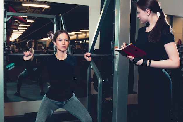 Female instructor evaluating fitness performance of young woman exercising at gym Free Photo