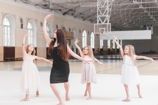Female instructor giving ballerina dance training to three girls Free Photo