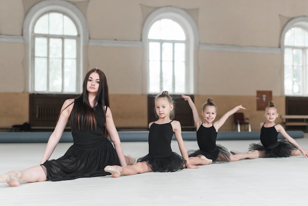 Female instructor sitting with three girls on floor in dance class Free Photo