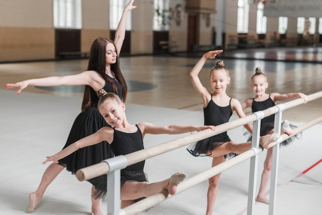 Female instructor teaching ballet dance to girls Free Photo