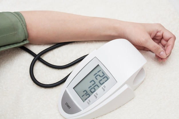 Female is taking care for health and measures her blood pressure Premium Photo