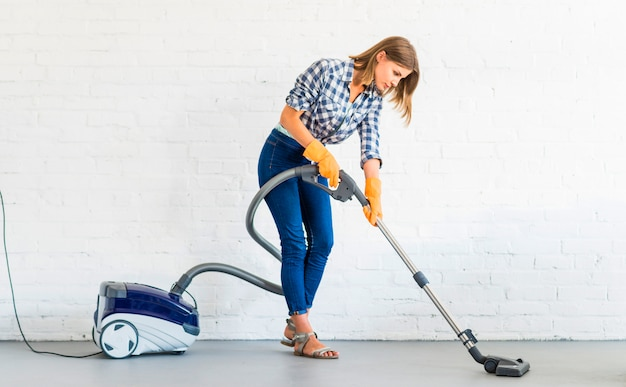 Female janitor cleaning floor with vacuum cleaner Free Photo