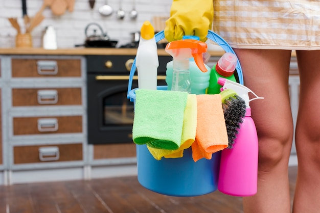 Female janitor holding cleaning accessories in bucket standing in kitchen Free Photo