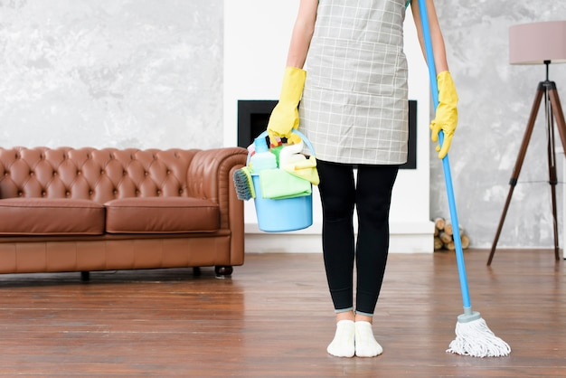 Female janitor standing at home holding cleaning products and mop in hand Free Photo