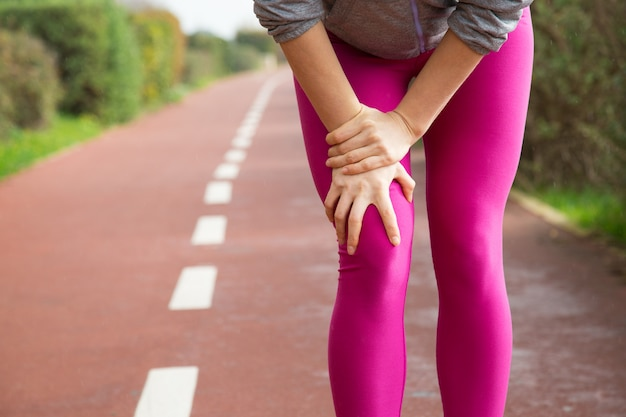 Female jogger wearing pink tights, injuring knee Free Photo