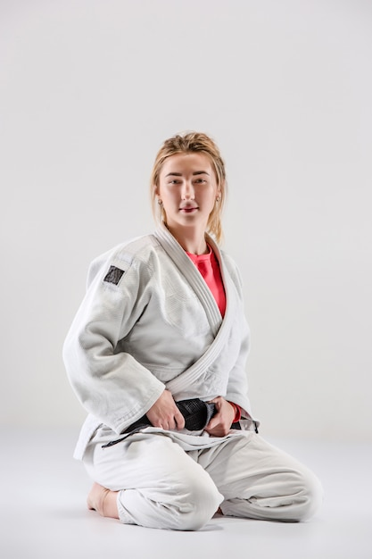 The female judokas fighter posing on gray Free Photo