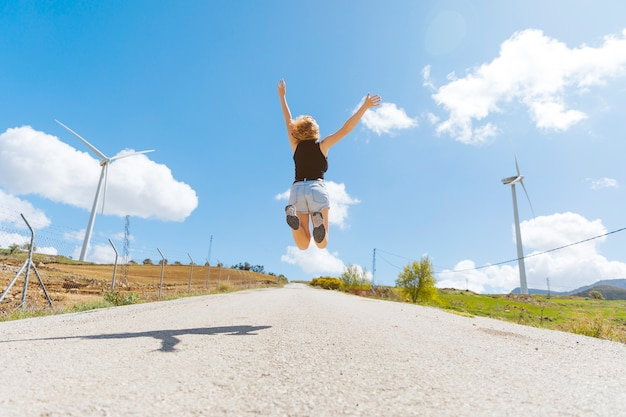 Female jumping on empty road Free Photo