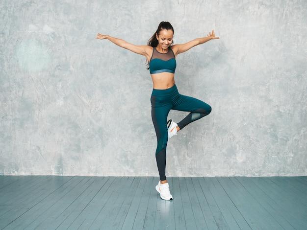 Female jumping in studio near gray wall Free Photo