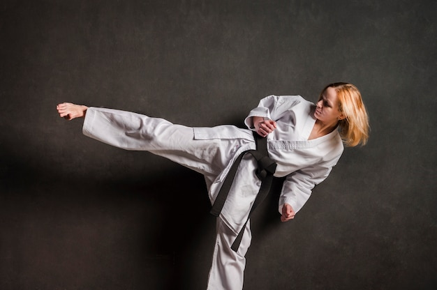 Female karate fighter kicking front view Free Photo