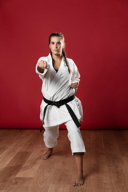 Female karate fighter performing punch isolated on red background Free Photo