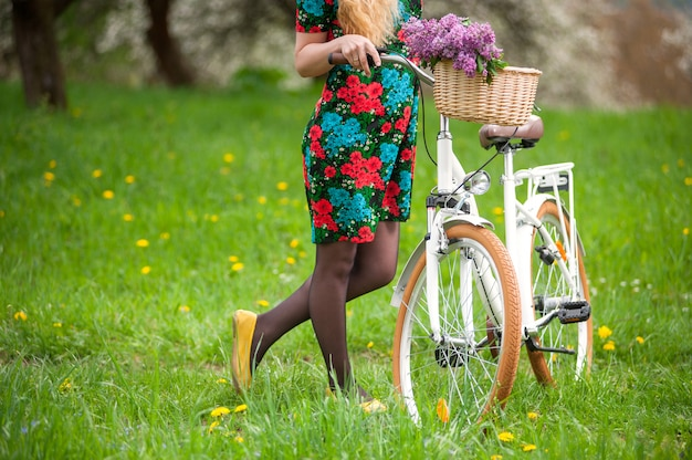 Female keeps retro white bicycle with lilac flowers Premium Photo