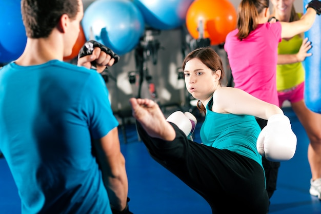 Female kick boxer with trainer in sparring Premium Photo