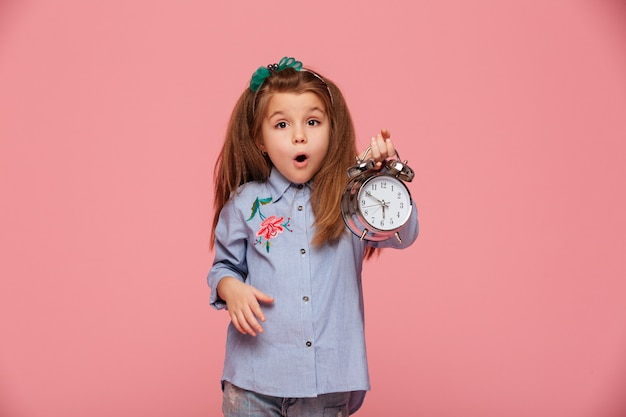 Девочка позирует с широко открытыми глазами и ртом, держа часы почти 6 в шоке или потрясен Бесплатные Фотографии