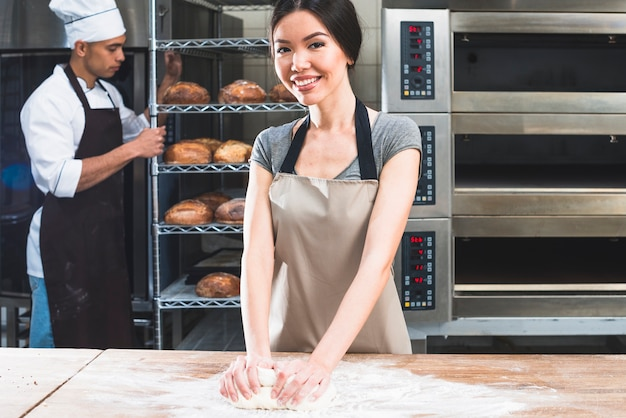 Female kneading the dough on wooden table and male baker holding baked bread shelves Free Photo