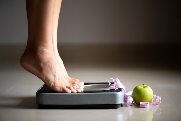 Female leg stepping on weigh scales with measuring tape and apple. Premium Photo
