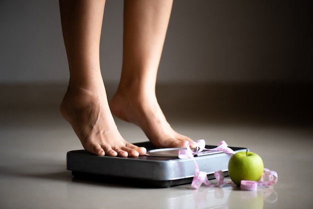 Female leg stepping on weigh scales with measuring tape and apple Premium Photo