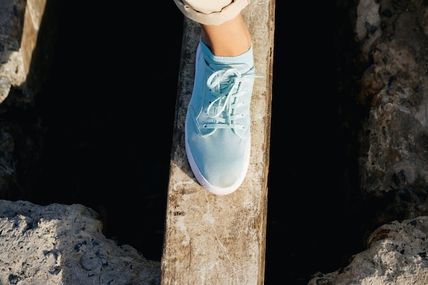 Female legs in beige pants and sneakers are on the board over the cliff Premium Photo