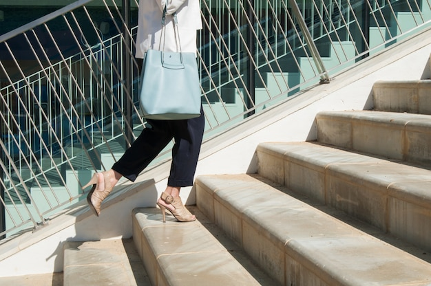 Female legs in black trousers with blue bag standing at stairs Free Photo