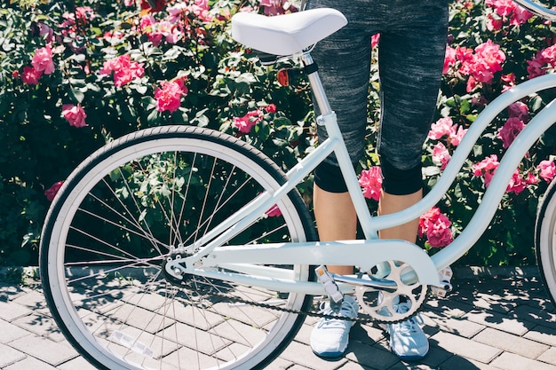Female legs in blue sneakers and a stylish bicycle against a background of bushes with roses Premium Photo