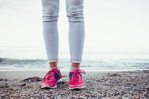 Женские ножки в розовых кроссовках стоят на пляже возле воды вечером Premium Фотографии