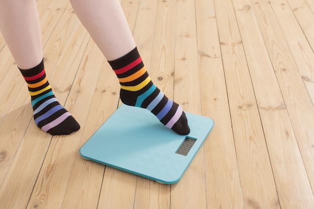 Женские ножки на электронных весах на деревянном полу Premium Фотографии
