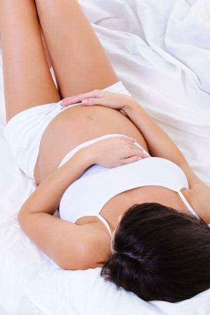 ベッドに横になっていると彼女のおなかをなでる女性 無料写真