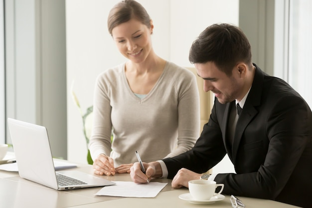 Female and male business leaders signing contract Free Photo