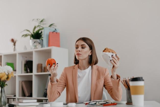 Responsabile femminile in posa in ufficio bianco. la signora guarda la mela con riluttanza, volendo mangiare un hamburger. Foto Gratuite