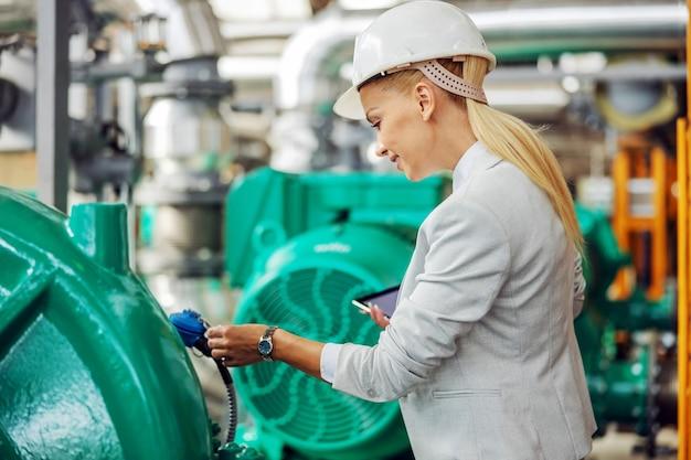 헬멧 손에 태블릿 난방 공장에 서 있고 터빈에 검사와 여성 관리자. 프리미엄 사진