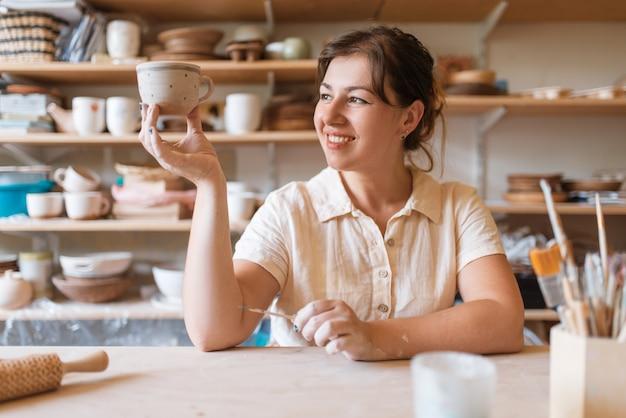 Мастерица держит свежий расписной горшок, гончарную мастерскую. женщина лепит миску. Premium Фотографии