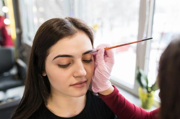 Il maestro femminile ha messo la vernice del sopracciglio nel salone di bellezza durante la procedura di trucco Foto Gratuite