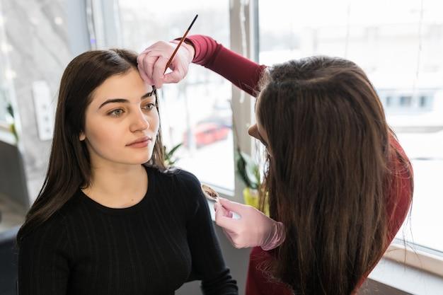Il maestro femminile ha messo la vernice per sopracciglia con il pennello durante la procedura di trucco Foto Gratuite
