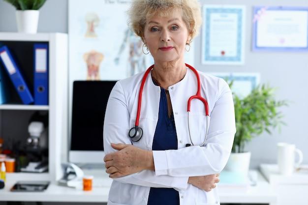 Female mature doctor against medical hospital Premium Photo