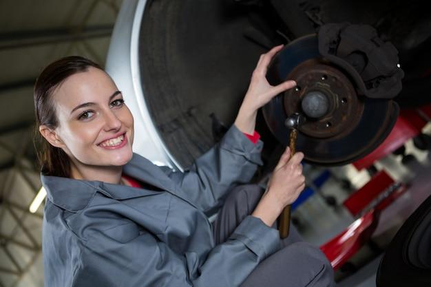 Female mechanic fixing car brake Free Photo