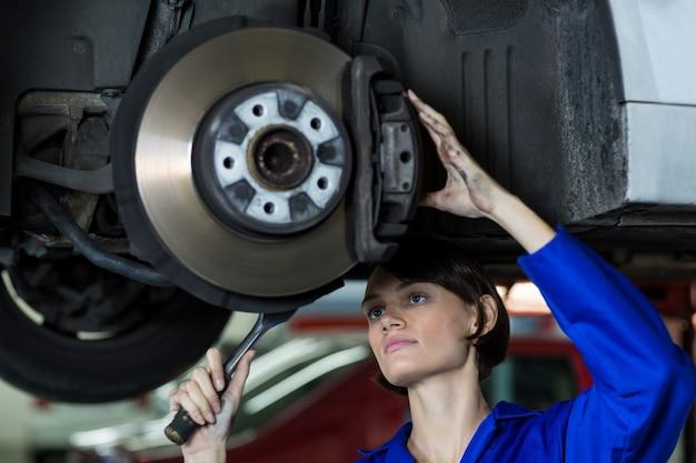 Female mechanic fixing a car wheel disc brake Free Photo
