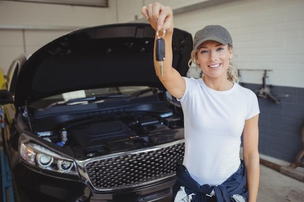 Женский механик в гараже, держа ключ от машины Бесплатные Фотографии