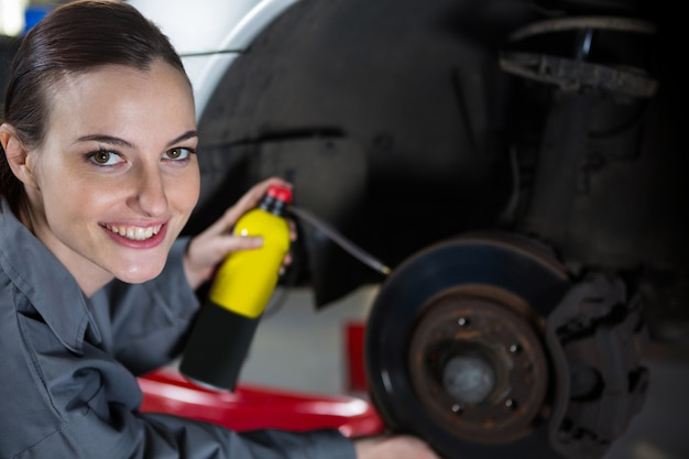 Female mechanic oiling car brake Free Photo