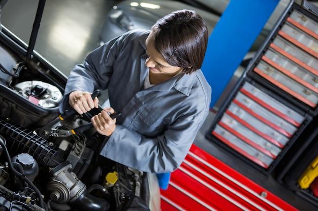 車にサービスを提供する女性メカニック 無料写真