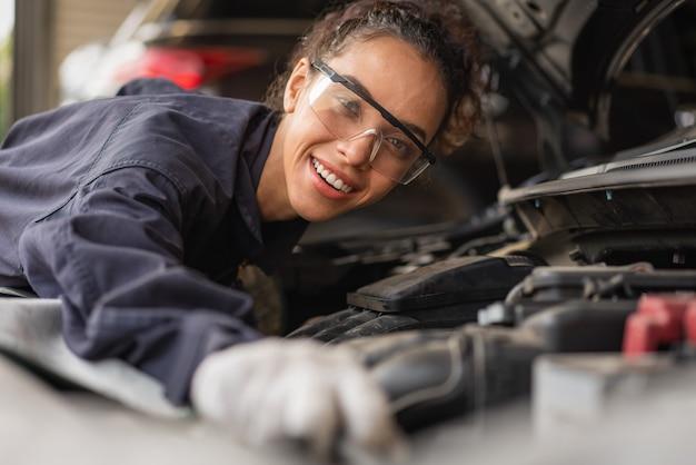 여성 정비공 미소 및 자동 서비스 차고에서 자동차 수리 유지 보수 작업 프리미엄 사진